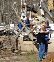 Gary Cross comforts his sister Charlotte Evans in front of the remains of the house where their sister Melissa Evans died near Crossville, TN